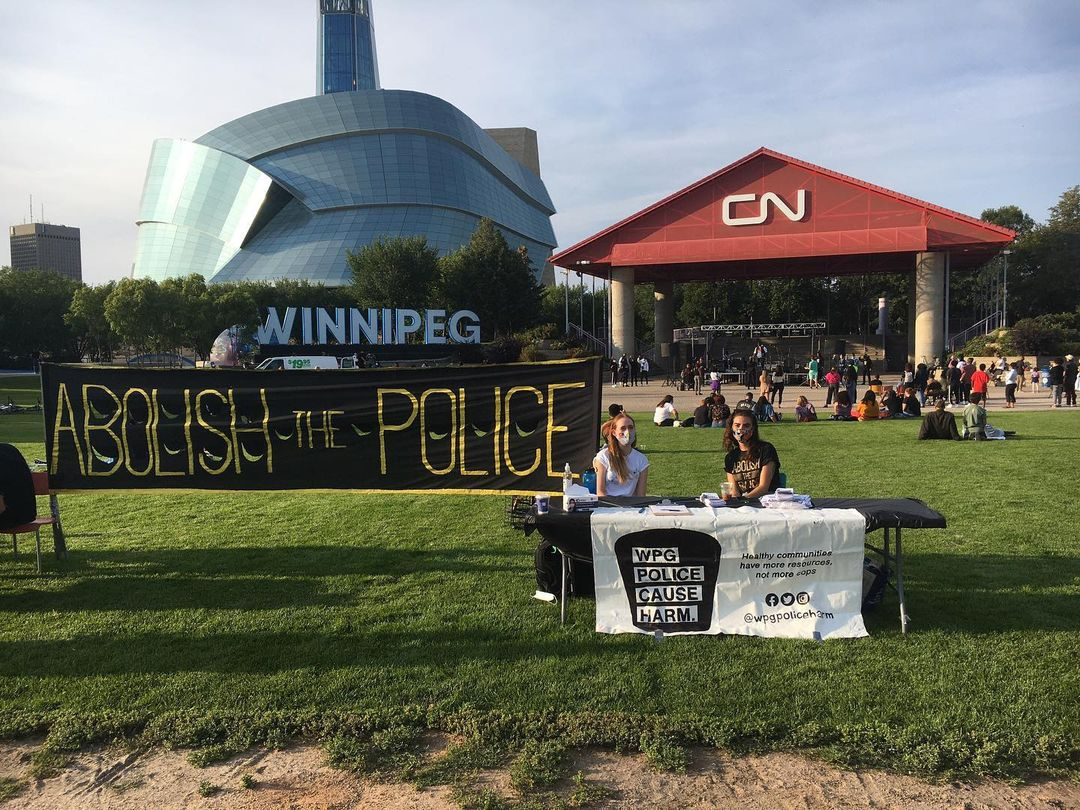 two members of winnipeg police cause harm at a police abolition info booth at the forks