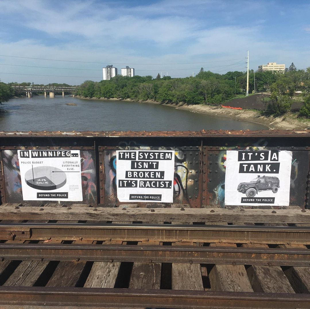 three police abolition posters on a bridge